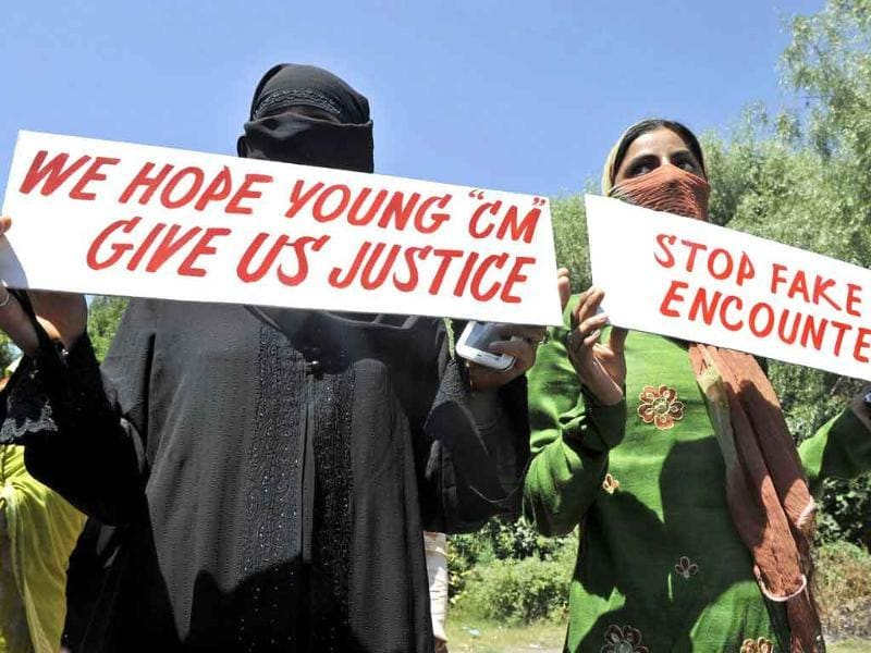 Kashmiri women hold up placards as they protest against fake encounters and custodial killings in Srinagar.