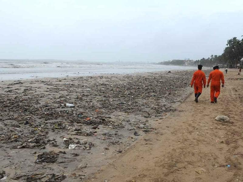 Indian coast guard officials walk past heaps of plastic and oil on Juhu Chowpatty beach in Mumbai
