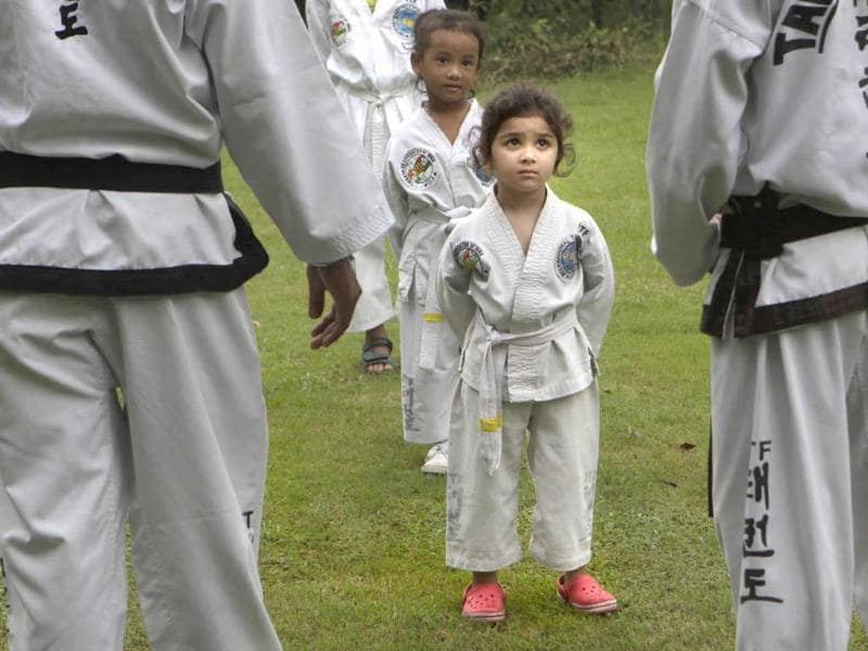 A young girl listens to instructions from her Taekwondo instructor during a practice session, in New Delhi.