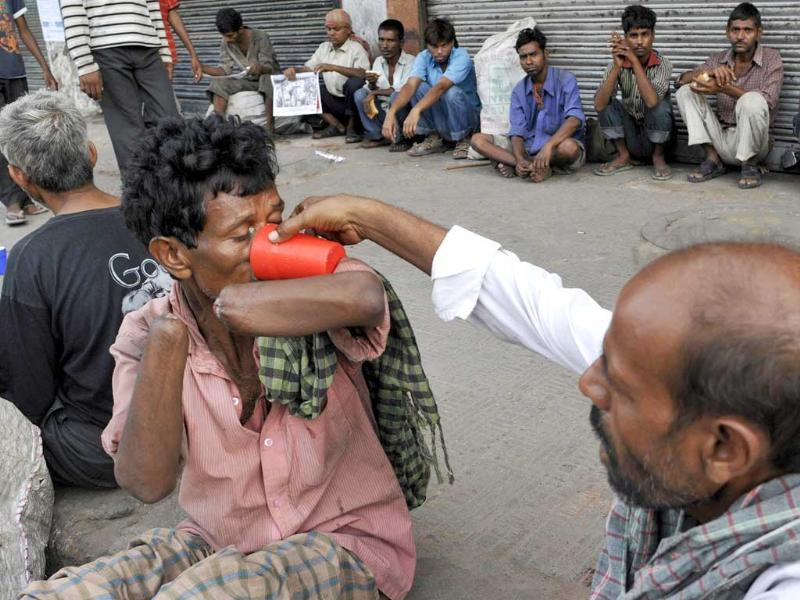 A man helps a physically disabled person to drink water in New Delhi.