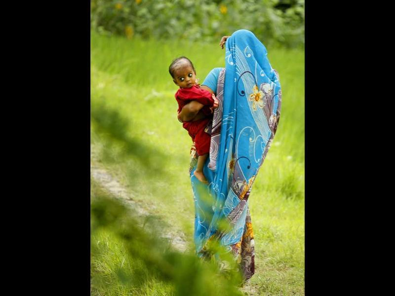 Woman holds a child and walks through a paddy field in Pawara village, Allahabad.