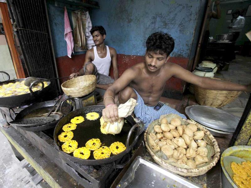 A snack vendor prepares deep fried sweets at his shop in Kolkata.
