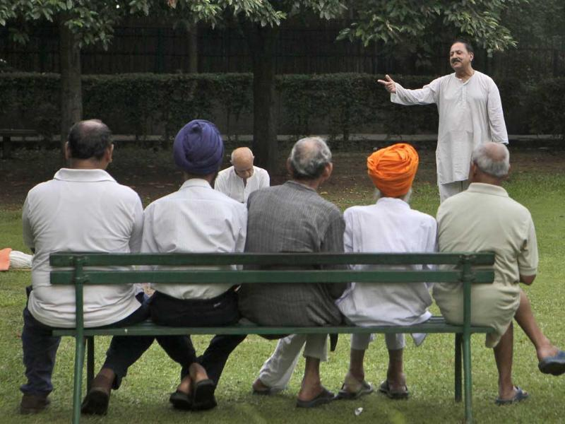 An elderly person sings a song as others sit and watch after daily morning exercise in a park, in New Delhi.