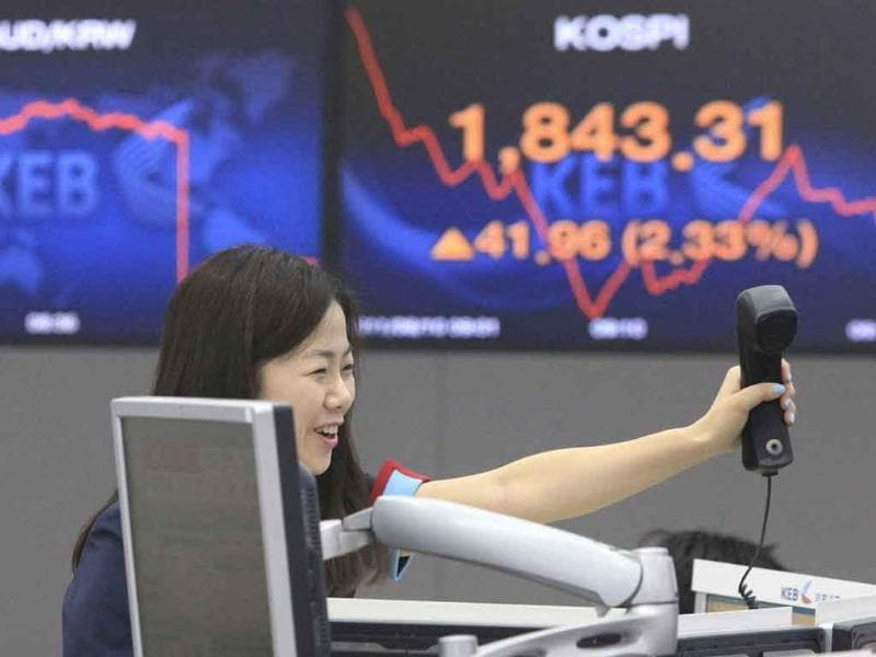A currency trader reacts in front of a screen showing the Korea Composite Stock Price Index in Seoul, South Korea.