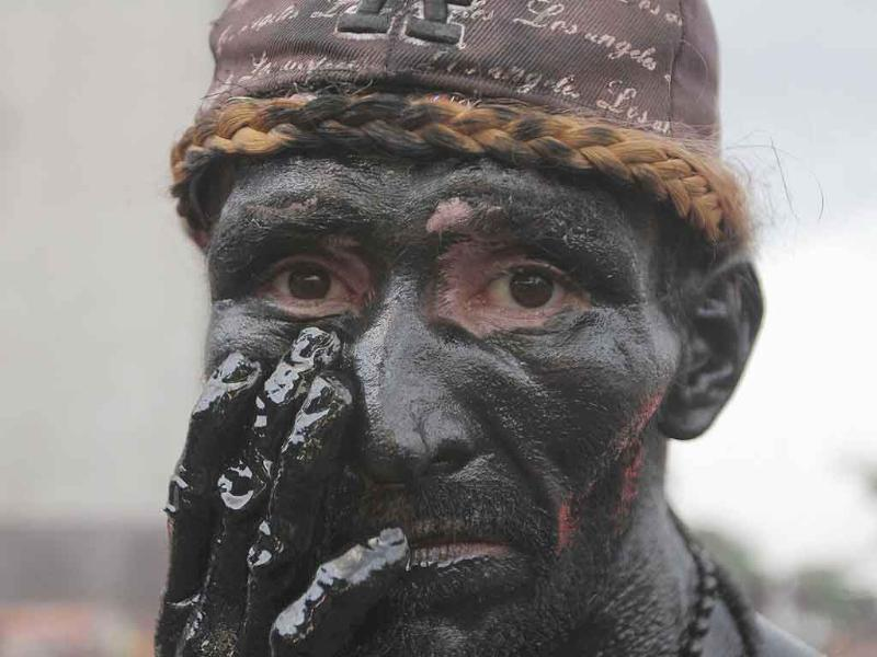 A devotee paints his face with motor oil to fulfil a promise he made for an answered prayer as he takes part in festivities honouring the capital's patron saint, Santo Domingo of Guzman, in Managua.