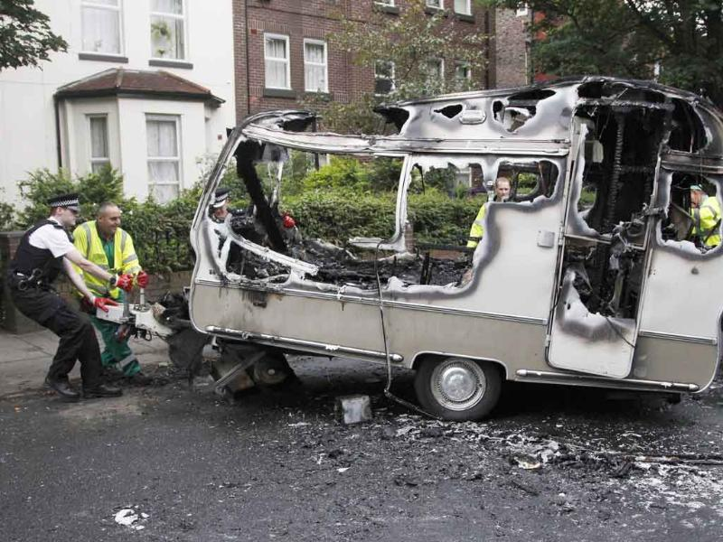 A police officer helps council workers to move the burned out shell of a camper, which was torched during overnight rioting and looting in the neighbourhood of Toxteth in Liverpool, northern England. British cities began to clean up shopping streets littered with debris from a night of looting by gangs of hooded youths copying the tactics of young Londoners who had rampaged through districts of the capital for three nights.