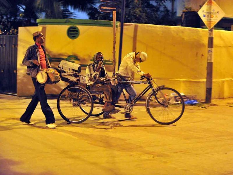 Visually impaired singer Mohammed Sheik Khaja Bhai (C) is pulled on a tricycle by his son Ahmed Bhai (R) and drummer Mohammed Haji Bhai (L) as they roam the streets of the old city in Hyderabad in the early hours during the holy fasting month of Ramadan.