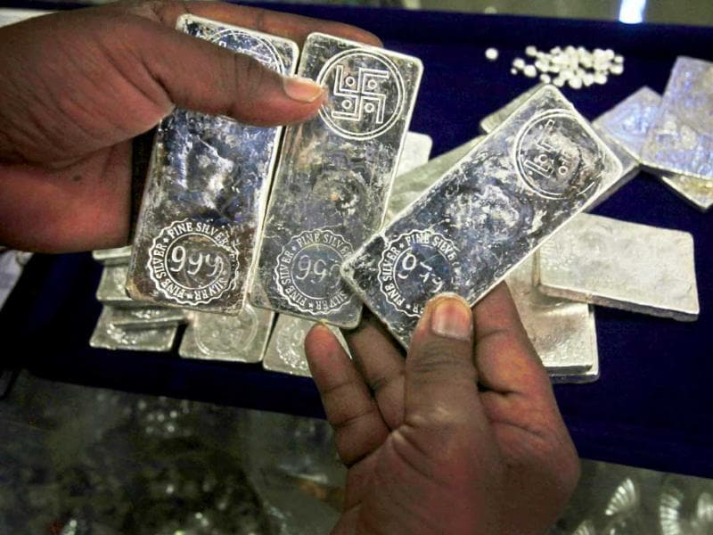 An Indian shopkeeper checks silver bars with the auspicious Hindu Swastika symbols, before weighing them at a shop in Hyderabad.