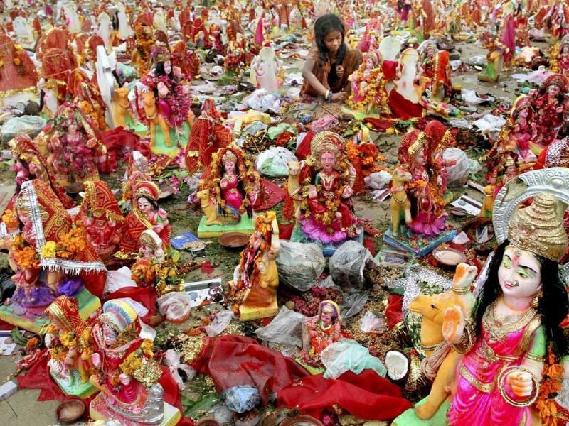 An Indian girl looks for reusable material amid idols of Hindu Goddess Dashama on the banks of River Sabarmati in Ahmedabad.