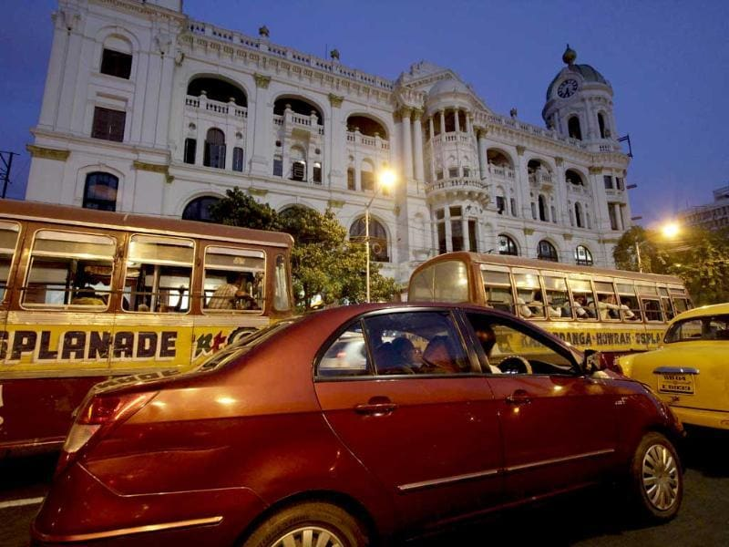 Vehicles drive past a heritage building in Kolkata.