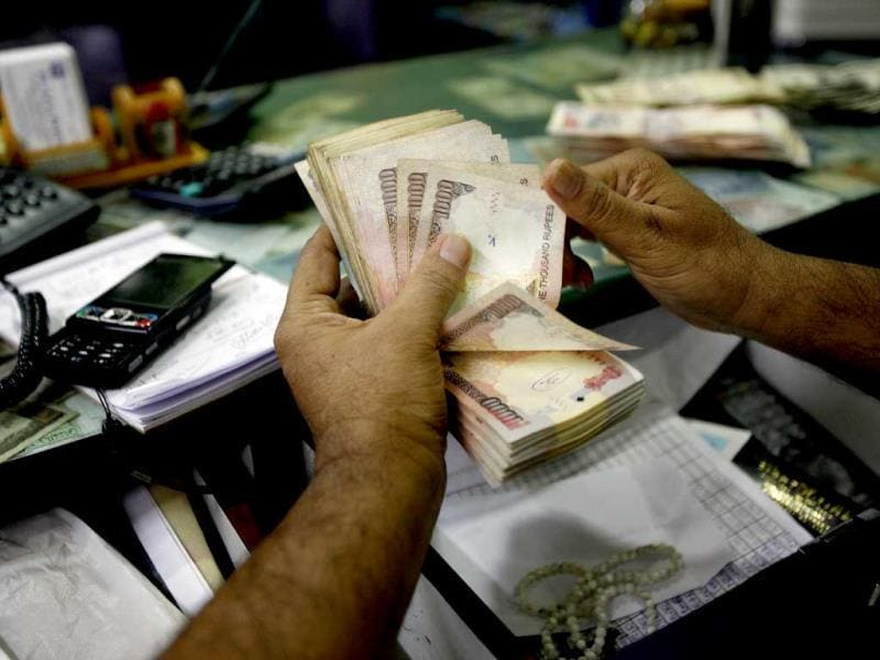 An agent at a money changing outlet counts Indian currency notes in Bangalore. (AP: File photo)