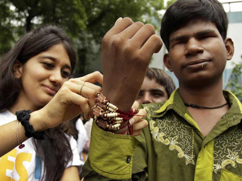 A volunteer ties a friendship band on a wrist of a blind man during Friendship Day celebrations at the Blind People Association in Ahmedabad.