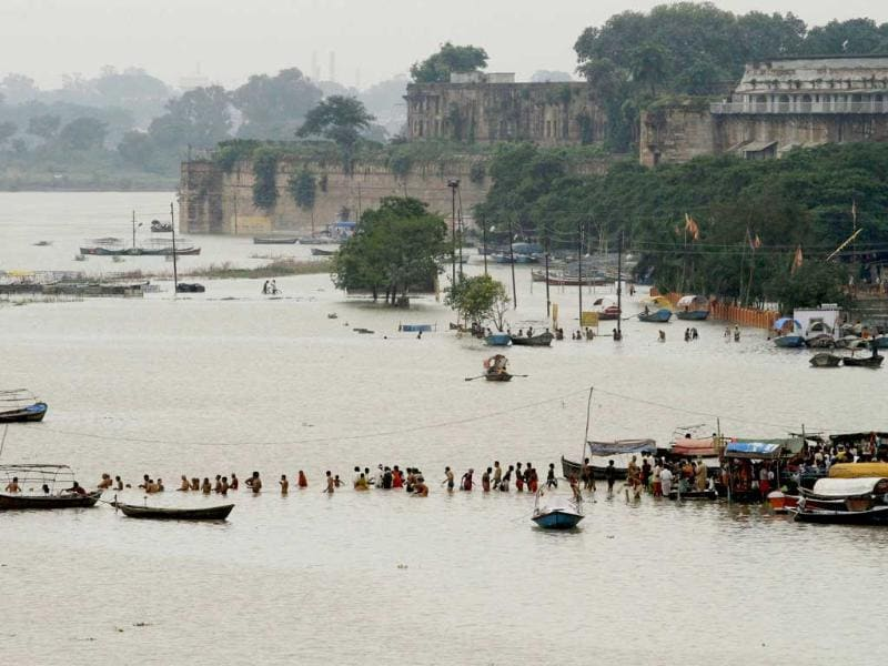 Hindu devotees take holy dip in the River Ganges after water level rose due to heavy rainfall in Allahabad.