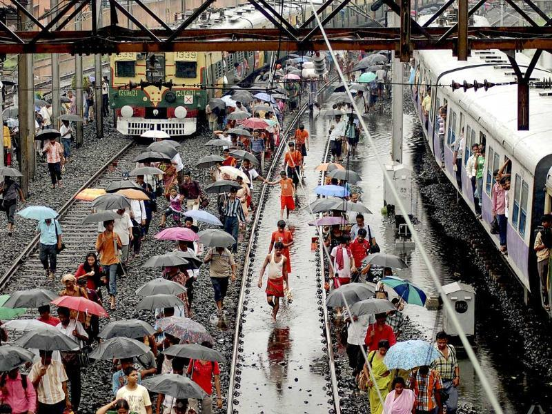 Train passengers walk after rail tracks submerged in rain water between Howrah and Lilua railway stations near Kolkata.