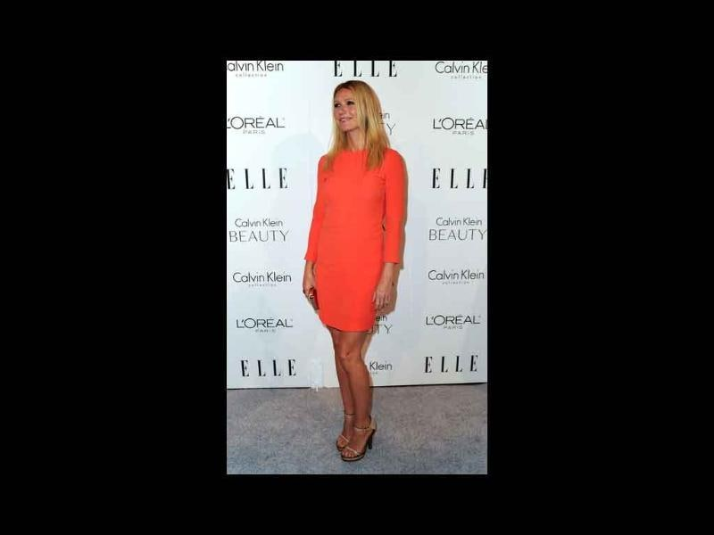 Gwyneth Paltrow doesn't impress with chunky, strappy shoes and searing orange dress, all by Calvin Klein.