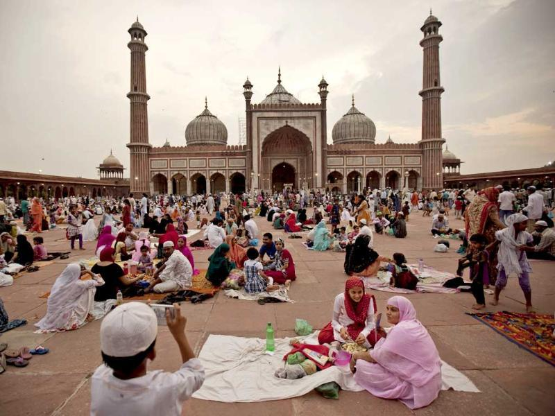 An muslim boy takes a picture of his mother and sister as they wait with their food to break the Ramadan fast at the Jama Masjid in New Delhi.
