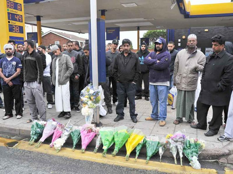 Residents stand by flowers laid at the crime scene where Haroon Jahan and two other Asian men were hit by a car and killed in the early hours Wednesday in Birmingham, central England.