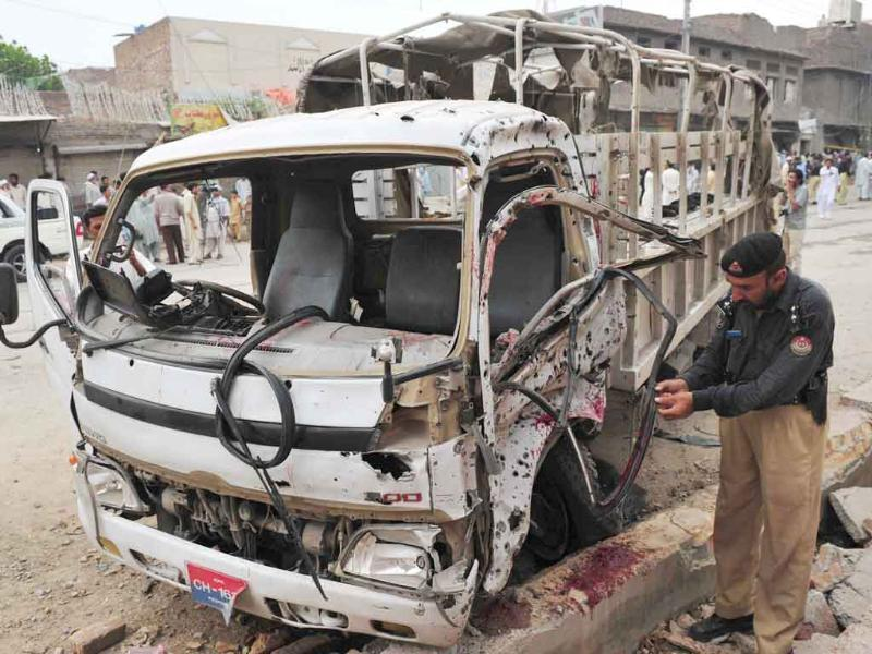 A Pakistani policeman inspects the wreckage of a police van following a bomb explosion in Peshawar. Bombers killed up to six people in the Pakistani city of Peshawar, where a woman suicide attacker blew herself up and roadside explosives struck a police vehicle, officials said.