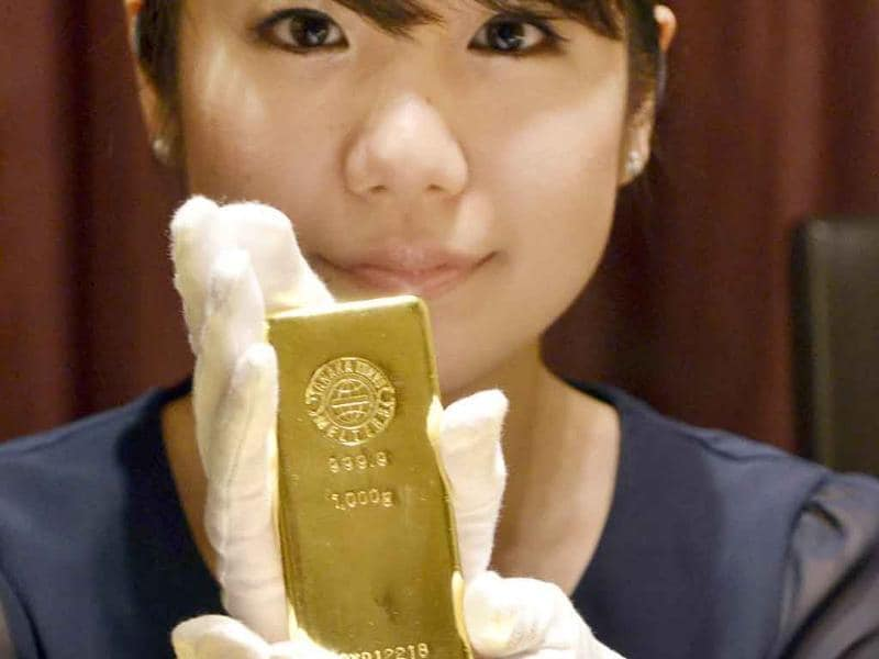 An employee of Japanese jeweller Tanaka Kikinzoku poses with 1-kilogram gold bars at the company's main shop in Tokyo. Gold prices surged past $1,800 an ounce as investors bought up the safe haven as markets around the world slump due to ongoing fears about the global economy.