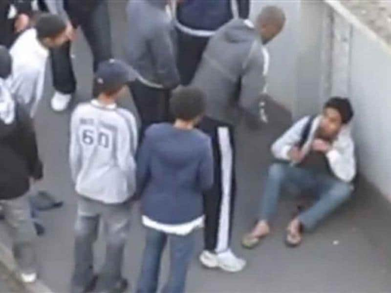 In this image from amateur video, a gang of youths in Barking, East London stand over Malaysian accountancy student Mohammed Asyraf Haziq, 20, who had been attacked and mugged in the street by an earlier group during rioting.