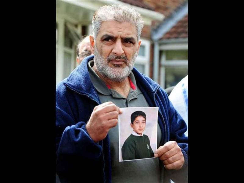 Tariq Jahan holds a picture of his son Haroon Jahan in Birmingham, England. Haroon Jahan died after being knocked down Tuesday by a car along with two other men while protecting their community from looters.