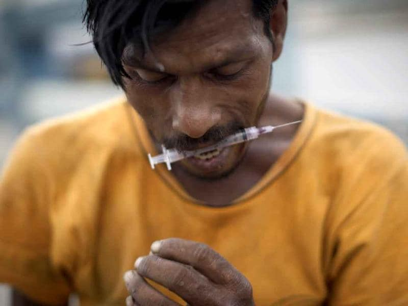 Pakistani drug addict Maqsood, 33, holds a syringe with his teeth after injecting heroin on a street in