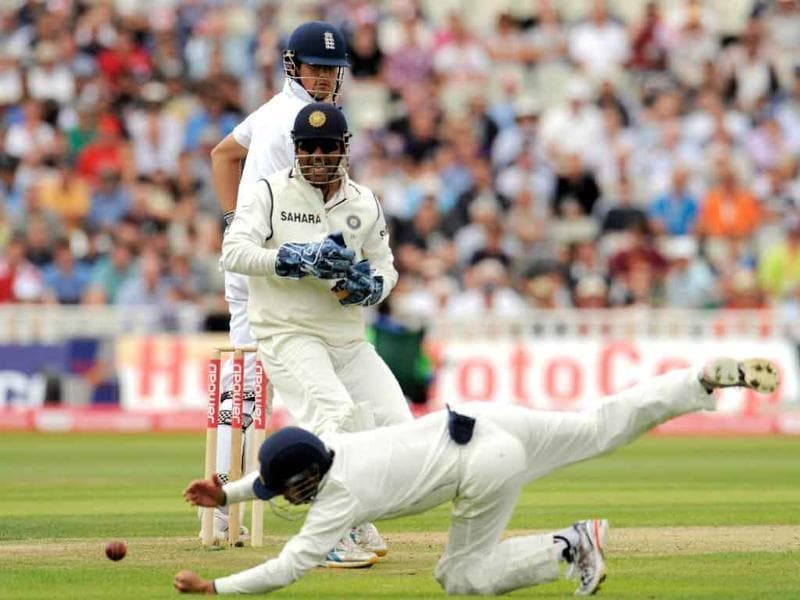 England's Alastair Cook (top) watches after hitting the ball past India's Gautam Gambhir as teammate Mahendra Singh Dhoni (C) looks on during their third cricket Test match at Edgbaston cricket ground in Birmingham, England.