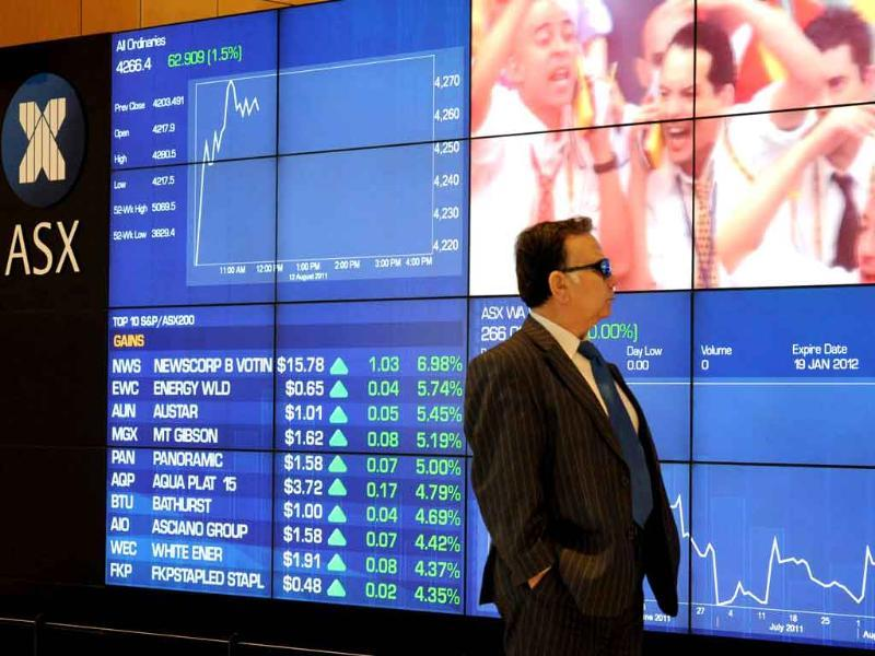 An investor watches market indices monitors on the Australian Stock Exchange (ASX) in Sydney. Australian stocks rose 1.3% at the opening following strong rallies in Europe and the United States.