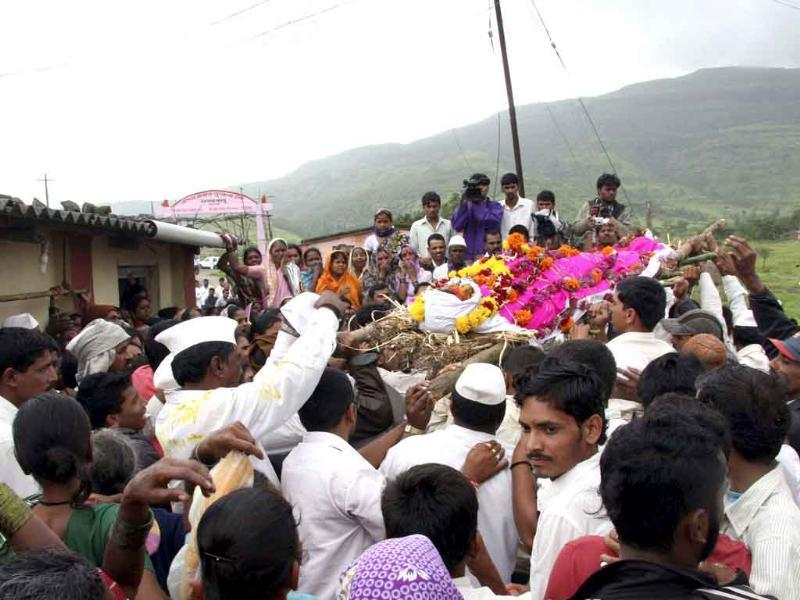 Mourners carry the body of a farmer, killed by police action during a protest, before a cremation ceremony in Maval village in Pune.