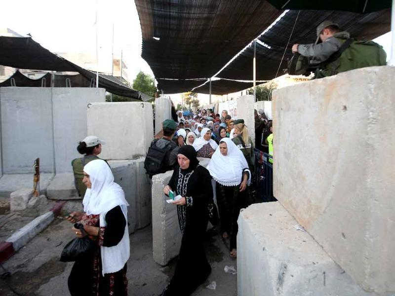 Palestinian Muslims cross through a barricaded Israeli checkpoint on the outskirts of Bethlehem into Jerusalem to attend the second Friday prayers of the holy fasting month of Ramadan at the Al-Aqsa mosque compound.
