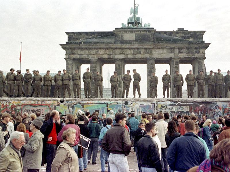 A file photo shows East Berlin border guards standing atop the Berlin Wall in front of the Brandeburg Gate.