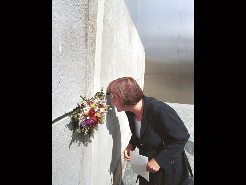 Chancellor of Germany, Angela Merkel looking through a peephole to view the death strip at the new Berlin Wall Memorial prior to the opening ceremony on August 13, 1998.