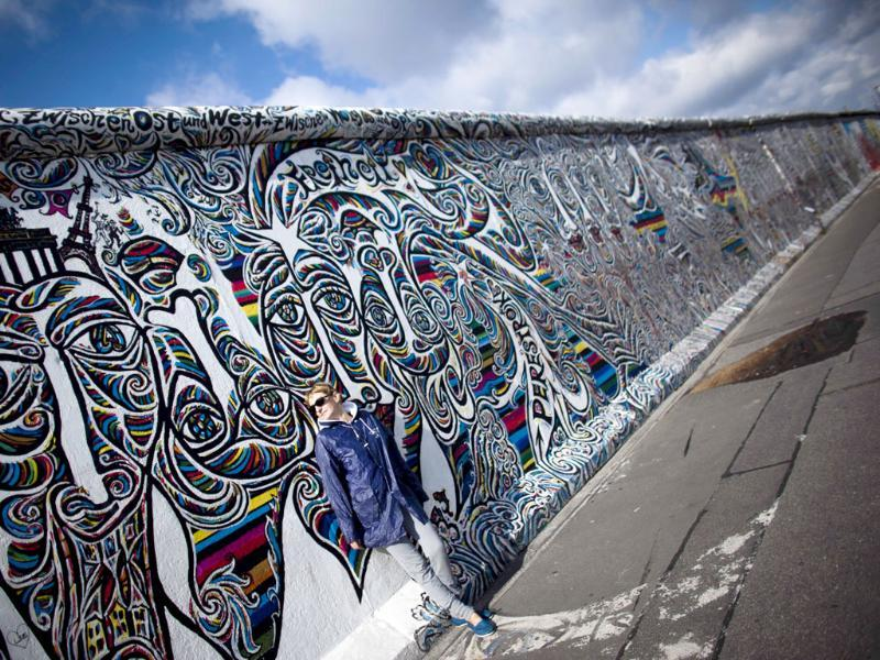 A tourist leans against a painted part of the former Berlin Wall named East Side Gallerie.