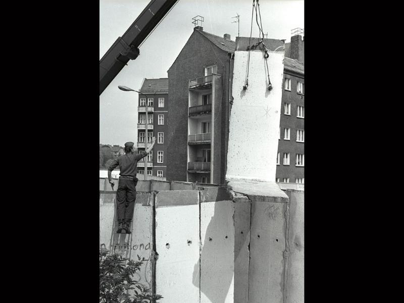 An East Berlin border guard standing on a ladder in West Berlin's Neukolln district on May 17, 1988, as he gives instructions to remove a part of the Berlin wall after East Berlin agreed to hand over a small portion of land to West Berlin.