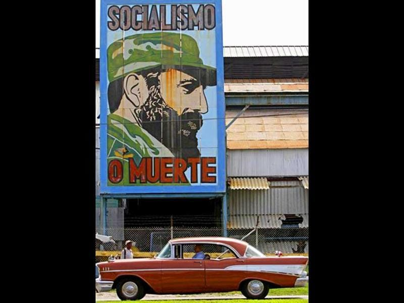 A car drives past a billboard showing Cuban leader Fidel Castro with the words reading in Spanish 'Socialism or death', in Havana, Cuba.