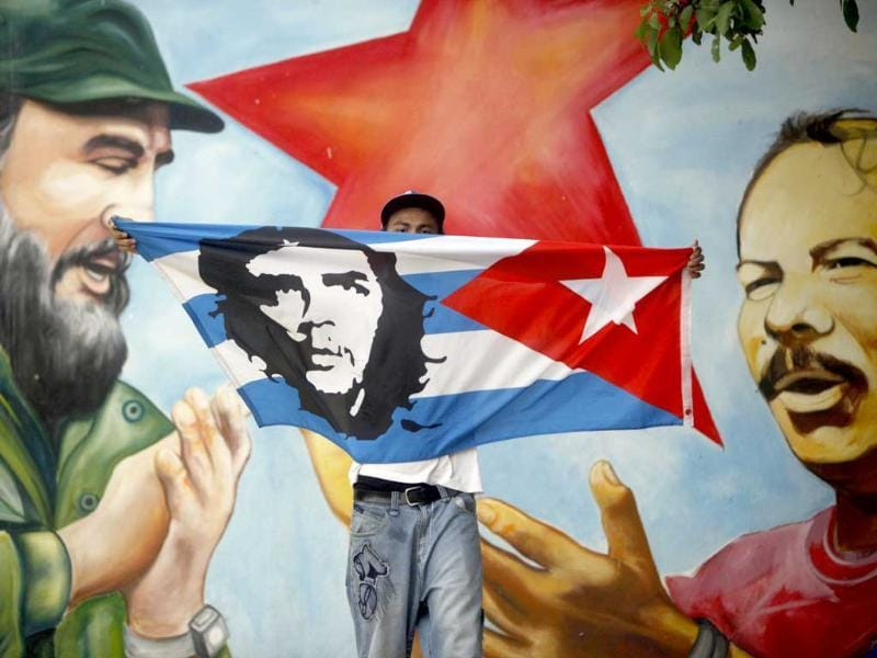 A man holds up a Cuban flag with the image of Cuba's revolutionary hero Ernesto