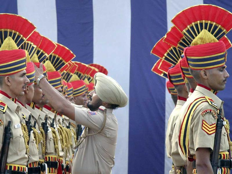 A policeman adjusts his colleague's headdress during a dress rehearsal ahead of Independence Day celebrations at the Red Fort in Delhi.
