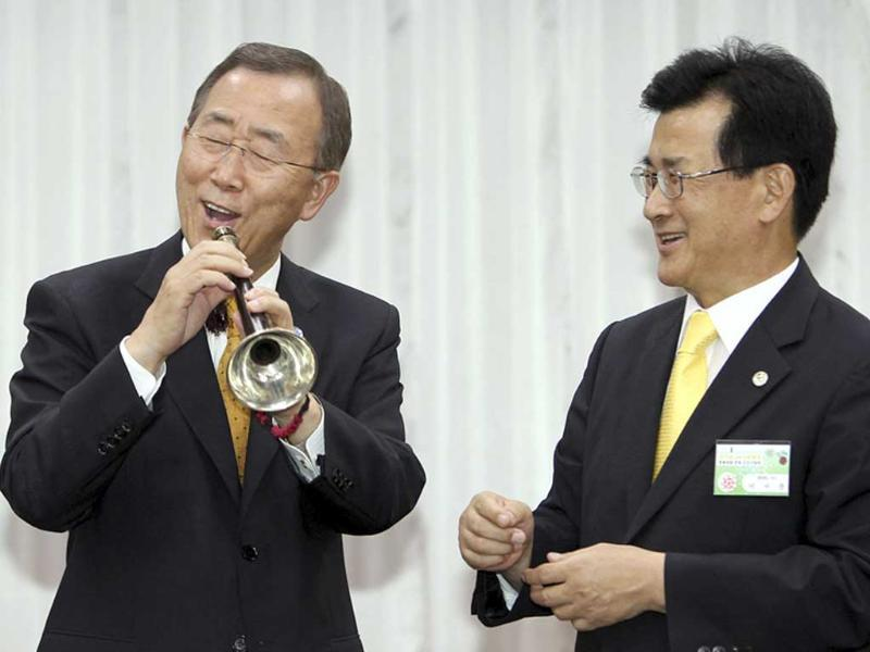 UN Secretary-General Ban Ki-moon reacts as he fails to play a Korean traditional pipe Taepyeongso after receiving it as a present from Lee Si-jong (R), governor of North Chungcheong province, during their luncheon meeting at a hotel in Chungju, southeast of Seoul. Ban is visiting his homeland South Korea for a six-day trip after he was re-elected as UN chief.