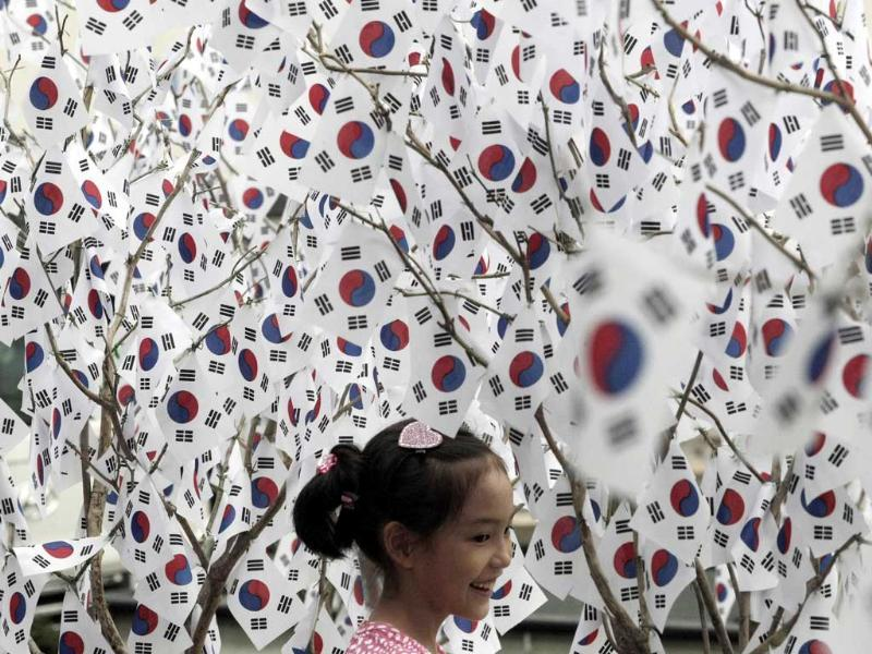 A girl is surrounded by small South Korean national flags set up to celebrate the Aug. 15 Korean Liberation Day from Japanese colonial rule in 1945, in Seoul, South Korea.