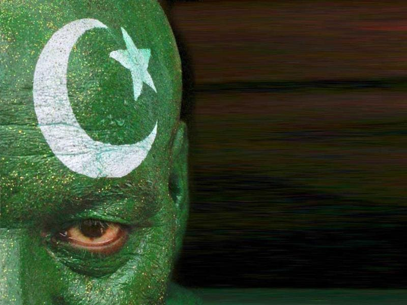 A man, with his face painted depicting the colours of the Pakistan national flag, attends a ceremony to mark the country's Independence Day at the Wagah border crossing with India on the outskirts of Lahore .