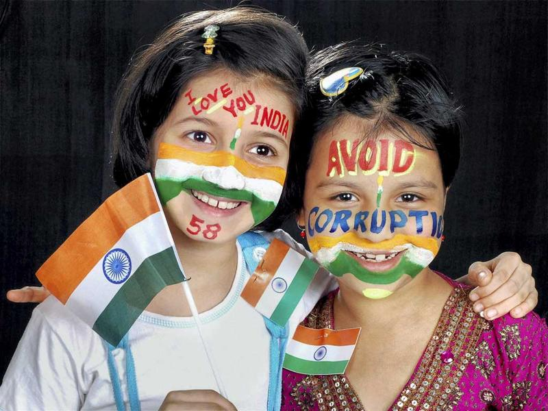 Children paint their faces and hold the National Flag on the eve of Independence Day in Hubli on Sunday.