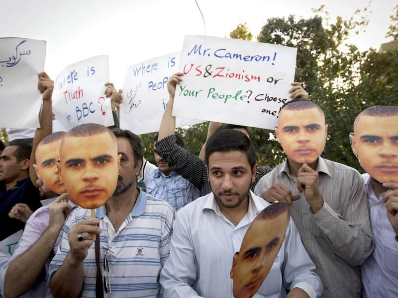 Iranian hardline students hold masks of Briton Mark Duggan, whose shooting by police sparked London's riots, during a demonstration outside the British embassy in Tehran to protest against what students called the