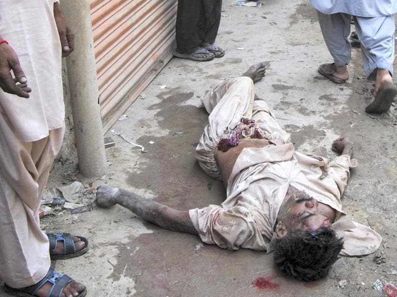 The body of victim, killed in a bomb blast, lies near the site of the attack in Dara Allah Yar, located in the Jaffarabad district of Balochistan province. A bomb ripped through a two-story hotel building in Pakistan's restive southwest, killing at least 11 people and wounding nearly 20, police said.