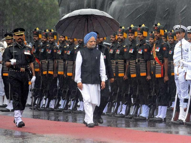 Prime Minister Manmohan Singh walks in a downpour of heavy rain as he inspects a guard of honour of troops prior to delivering a speech from the ramparts of The Red Fort in New Delhi on India's 65th Independence Day.