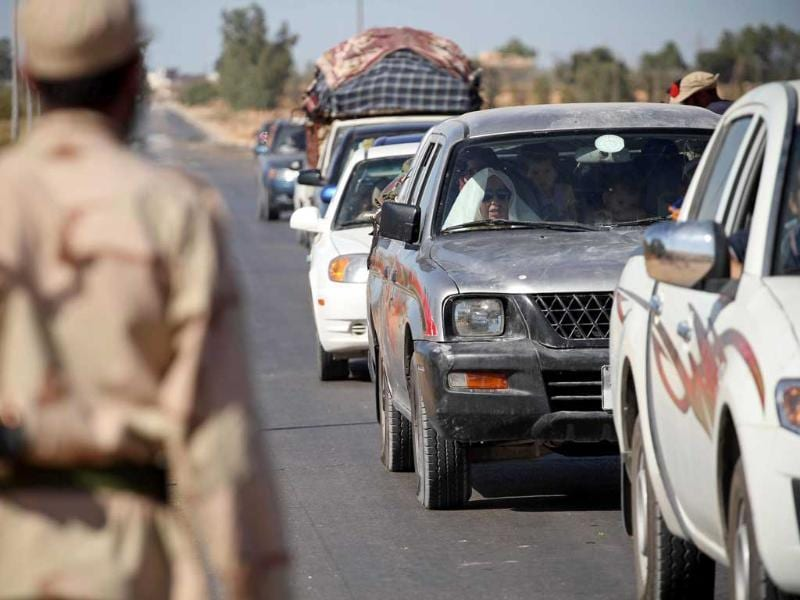 Libyan civilians fleeing the fighting between rebels and loyalist troops in Zawiya approach a checkpoint held by rebels 10 kms outside the town.