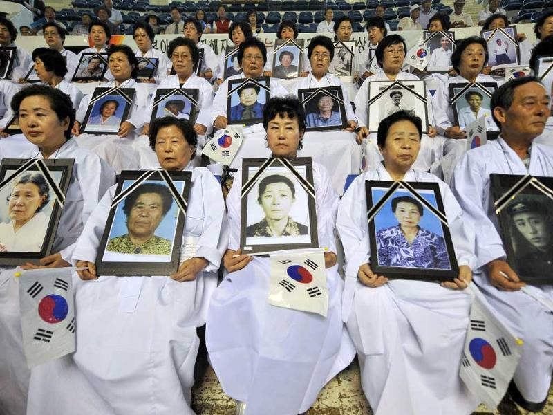 South Korean family members of victims of World War II hold portraits of family members during an anti-Japanese rally to commemorate the 66th anniversary of liberation from Japan's 1910-45 colonial rule in Seoul.