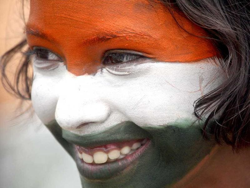 A school girl, with her face painted in the colours of national flag, takes part in a cultural program to celebrate Independence Day in Chandigarh.