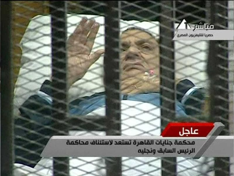 In this video image taken from Egyptian State Television 83-year-old former Egyptian president Hosni Mubarak gestures as he lies on a bed within a cage at the court building in Cairo.