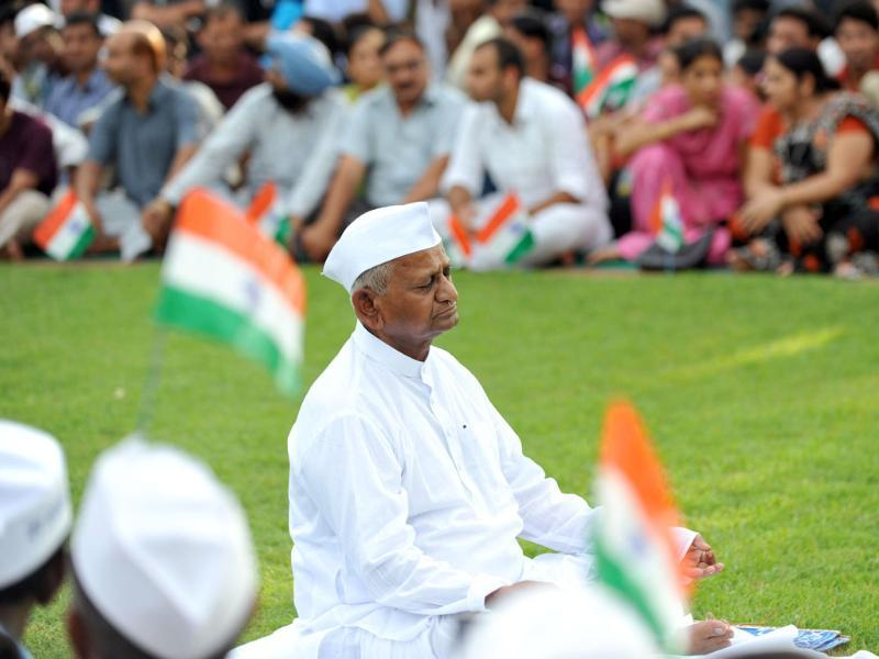 People wave the national flag as they surround 73-year old anti-corruption crusader Anna Hazare during a protest at Rajghat in New Delhi.