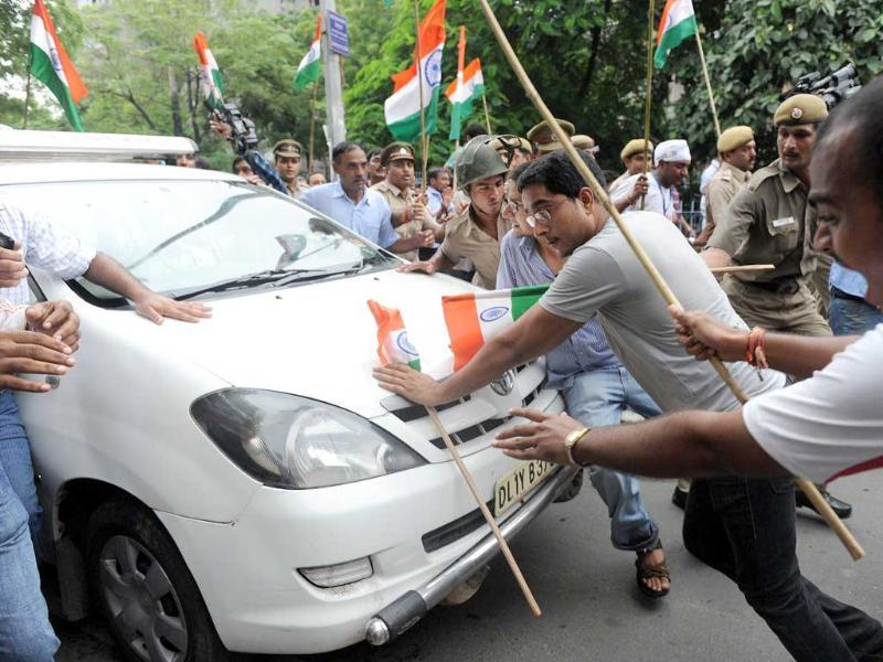 Supporters of social activist Anna Hazare attempt to halt the progress of a police vehicle in New Delhi.